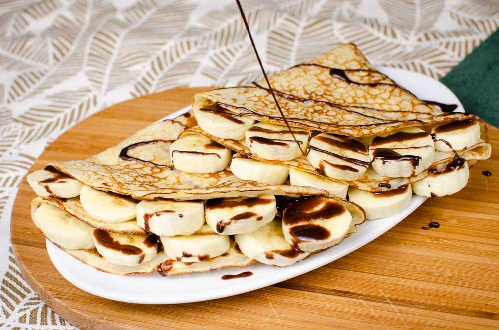 Two folded pancakes with slices of banana tucked inside served on a white plate on a brown wooden board and chocolate sauce being poured over the top