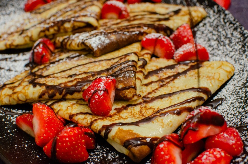 Drizzling easy chocolate sauce over English pancakes served with chopped strawberries on a black plate with icing sugar sprinkled over the top
