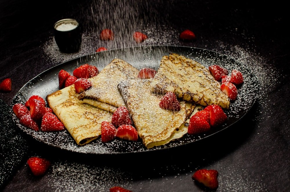 Four folded pancakes served on a black plate with scattered chopped strawberries on the plate and on the sides and icing sugar being sprinkled all over the top