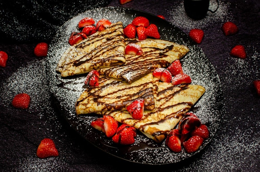 Four folded Easy English Pancakes served on a black plate with scattered chopped strawberries on the plate with sprinkled icing sugar and chocolate sauce on top