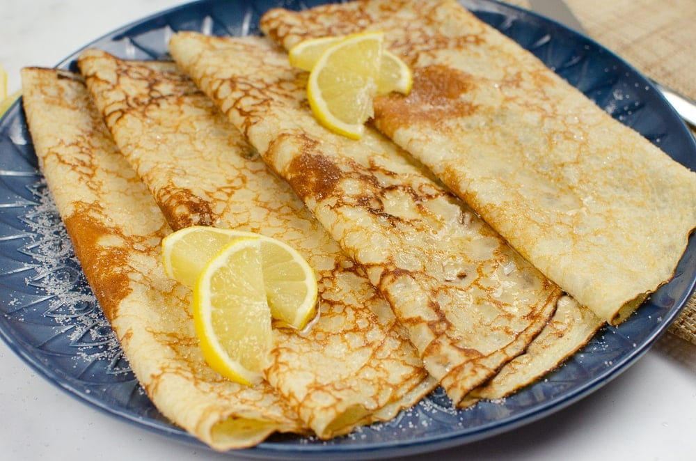 Four folded Easy Homemade English Pancakes served on a blue plate with lemon and sugar on top