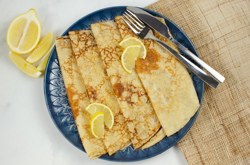 Four folded Easy Homemade crepes served on a blue plate with lemon and sugar on top with a silver knife and fork on the side with slices of lemon on the left side of the plate and a sheet of brown hessian to the right side of the plate