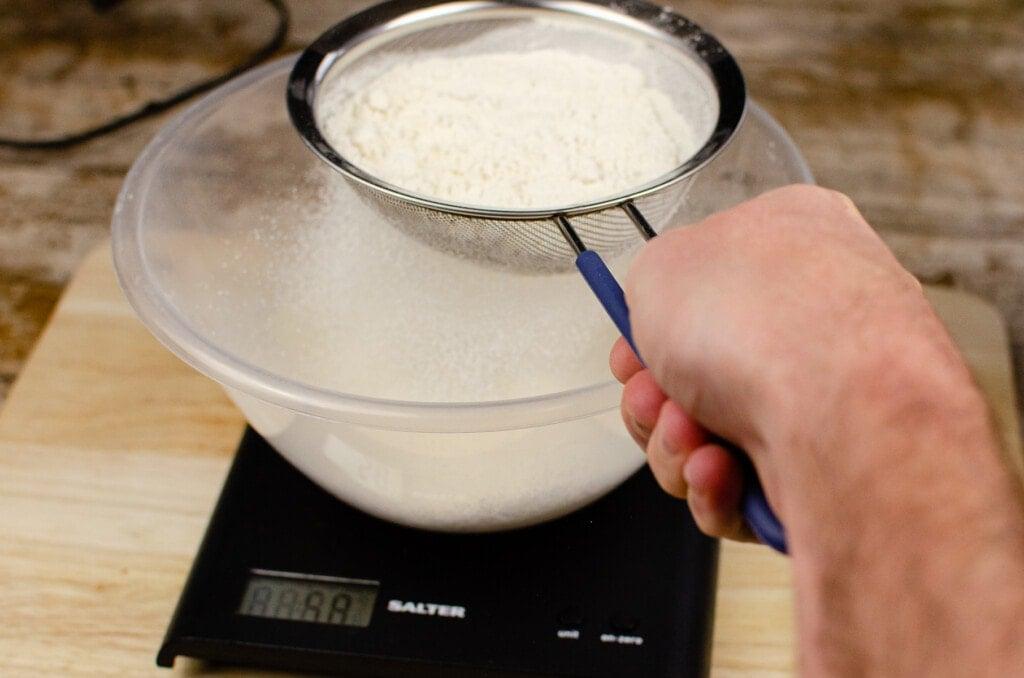 Sieving the plain flour into a clear plastic bowl