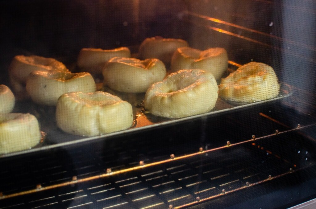 Flawless Yorkshire puddings starting to rise, cooking in the oven on a metal tray
