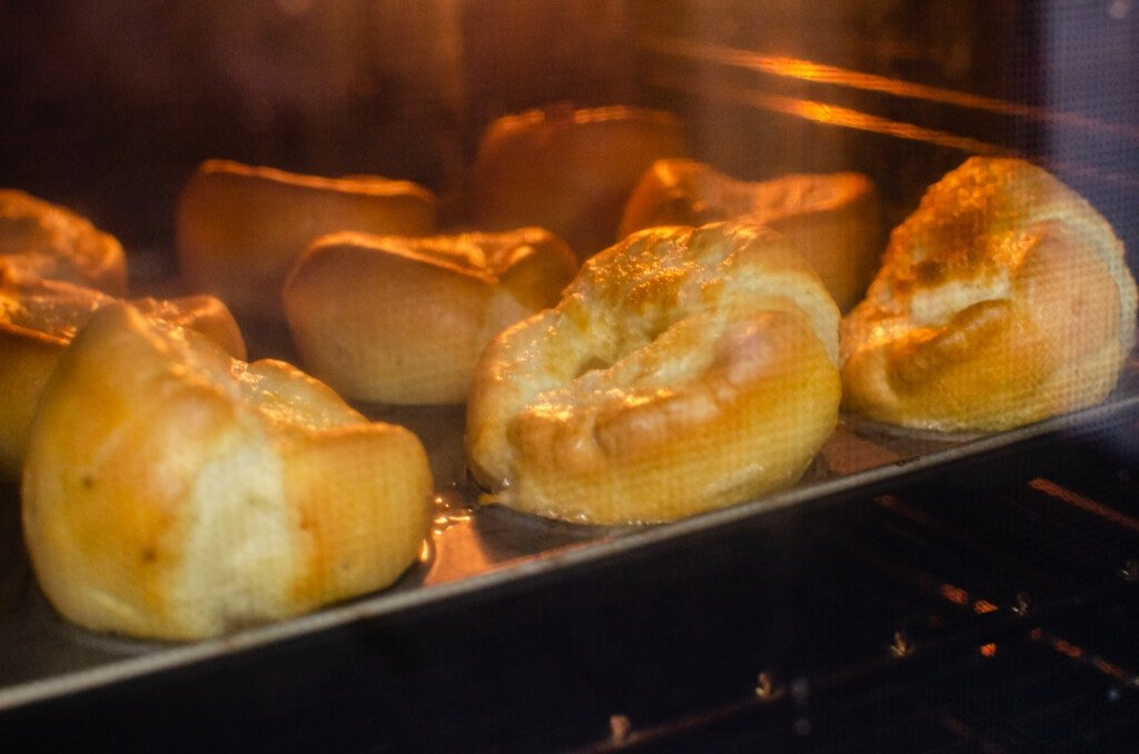 Flawless Yorkshire Puddings cooking in a baking tray and rising in the oven