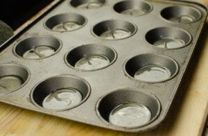 Hot sunflower oil in each section of the cupcake tray placed on a wooden chopping board