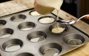 Pouring the yorkie pudding mixture into each section in the cupcake tray from a clear measuring jug and using a silver spoon to stop any drips