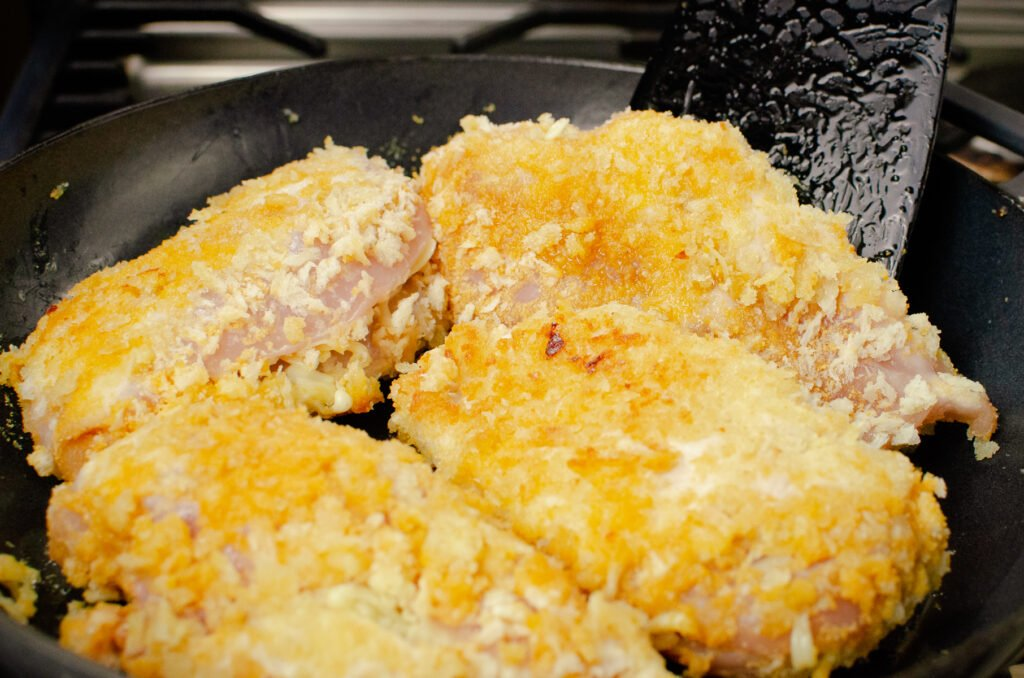 Turning over bread crumbed coated chicken breasts in a cast iron pan with a black spatula