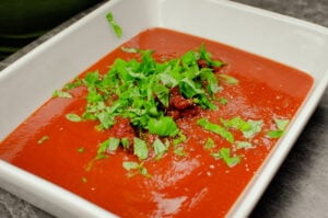 Fresh chopped basil and pepper added to the tomato passata sauce in a white casserole dish