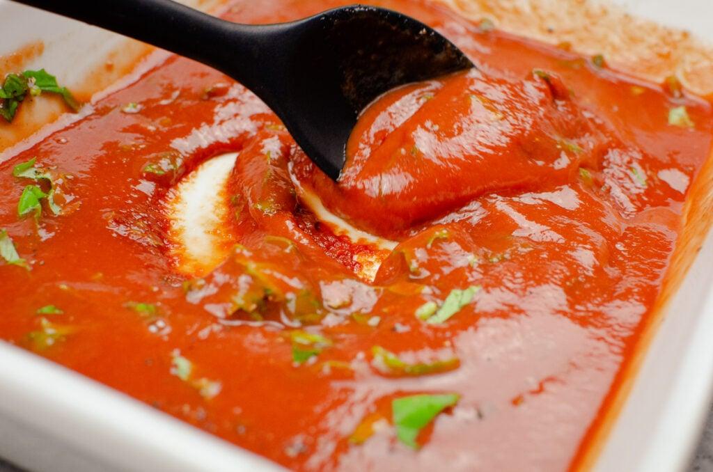 Stirring fresh chopped basil into tomato passata in a white casserole dish