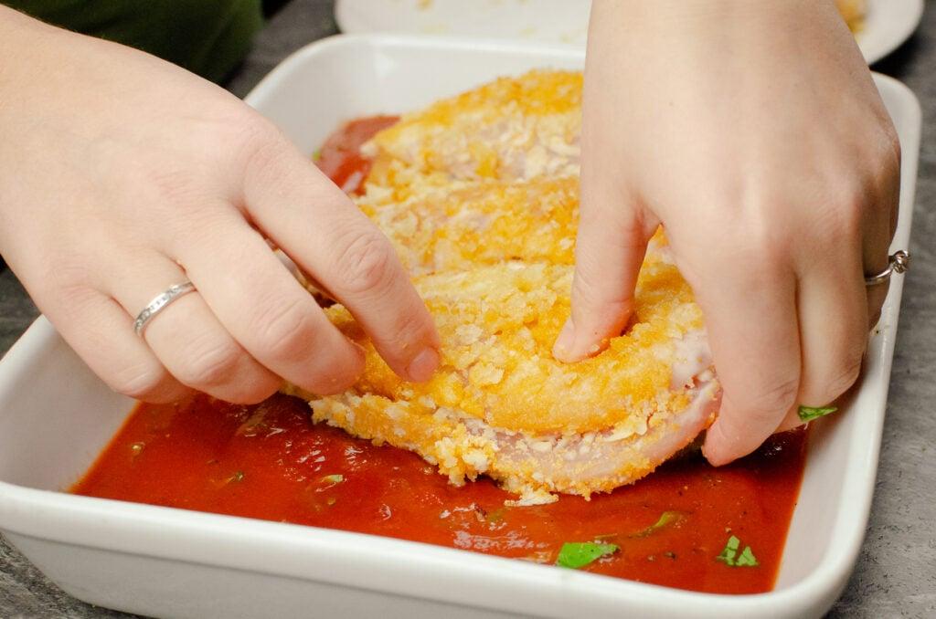 Placing stuffed mozzarella bread crumbed coated chicken breast by hands into tomato passata sauce in a white casserole dish