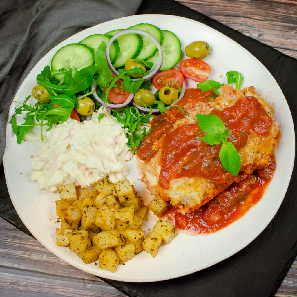 Crispy bread crumb mozzarella chicken served with tomato sauce , lettuce,red onion, tomatoes, green olives , coleslaw and potato squares on a white plate