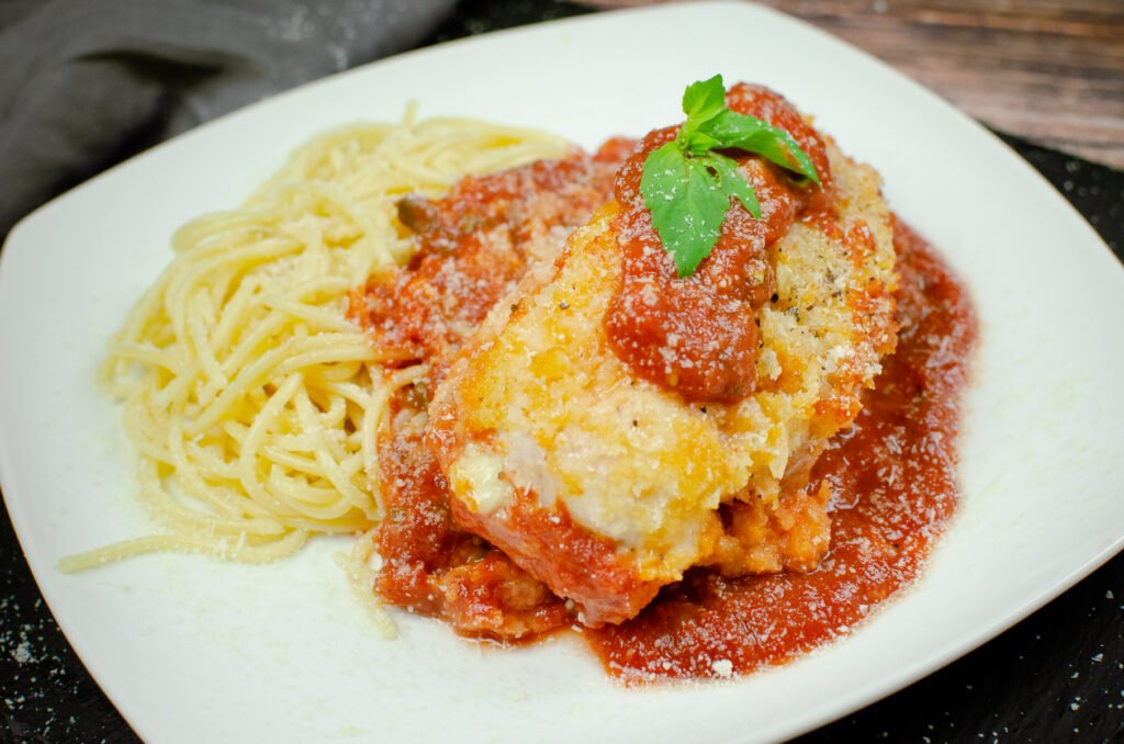Chicken parmesan served with tomato passata sauce and spaghetti on a white plate