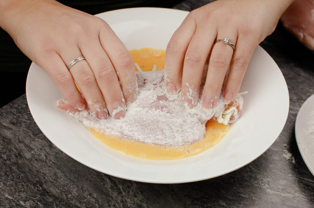 Dipping a flour dipped stuffed chicken breast into whisked egg in a white bowl