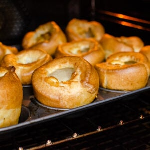 Flawless Yorkshire Puddings cooked in a cupcake tin on a metal rack in the oven
