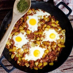 One pot Corned Beef Hash served in a cast iron pan with four eggs on top and a wooden spoon with chopped parsley on the side