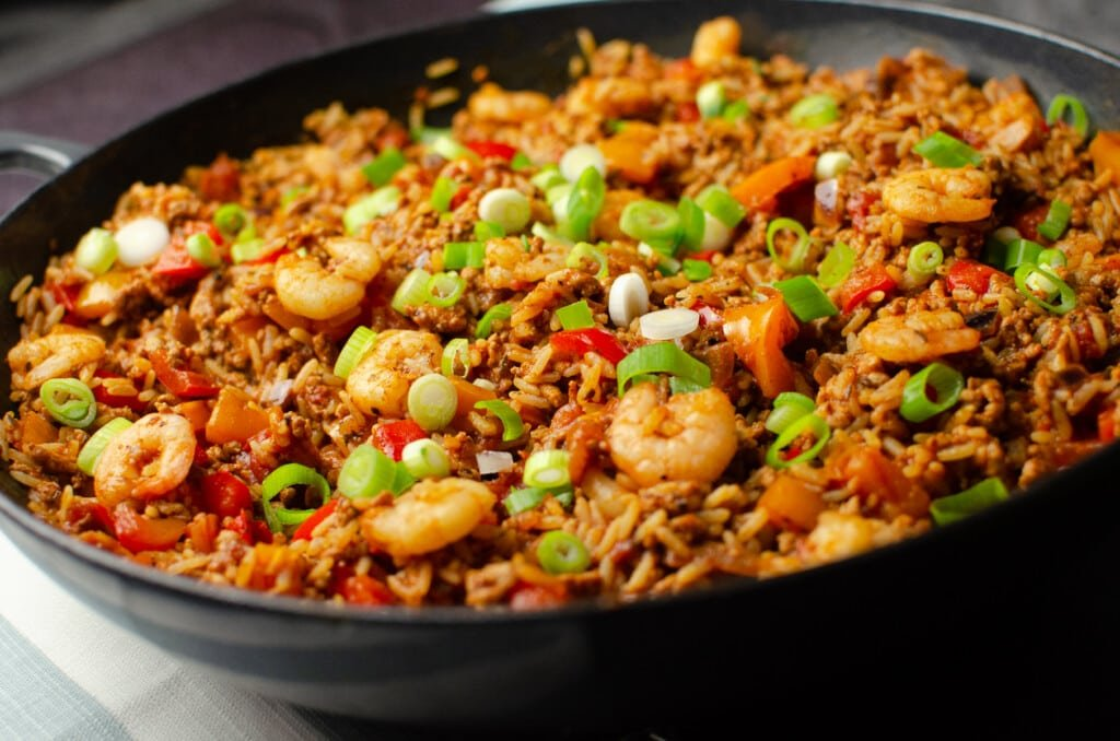 Pork and Prawn Jambalaya in a cast iron pan with chopped spring onion sprinkled over the top