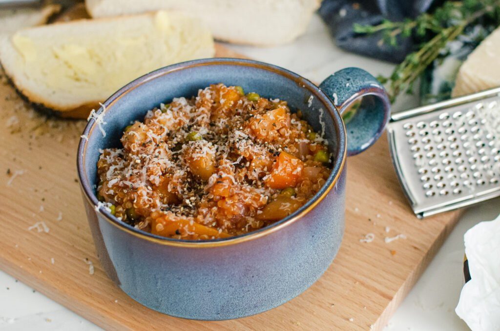 Quinoa Vegetable Stew served in a blue bowl with sprinkled parmesan cheese on top with crusty bread and a silver grater on the side