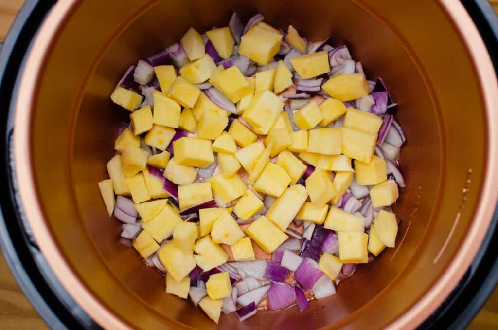 Chopped swede and red onion frying in olive oil in a pressure cooker pot