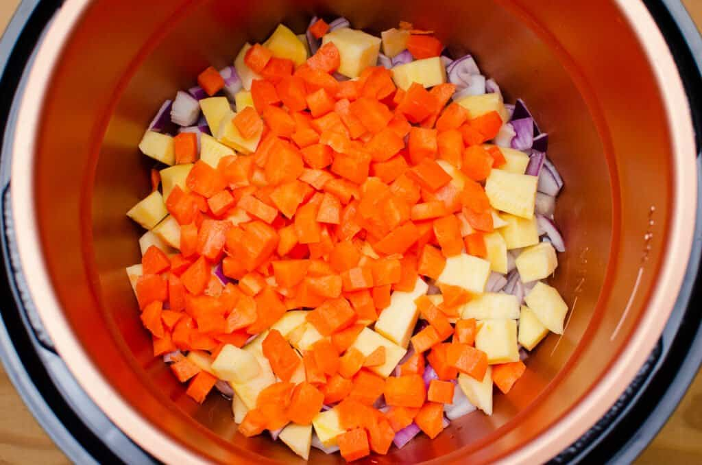 Chopped Carrot, Swede and red onion frying in olive oil in a pressure cooker pot