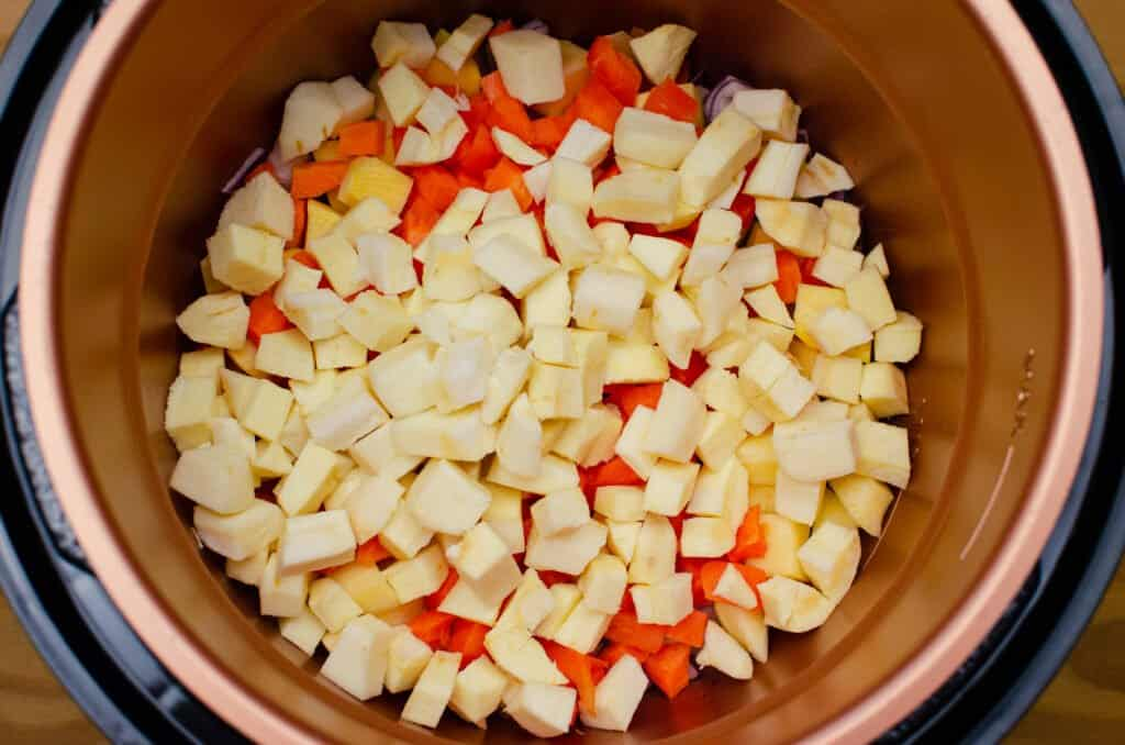 Chopped Parsnip, Carrot, Swede and red onion frying in olive oil in a pressure cooker pot