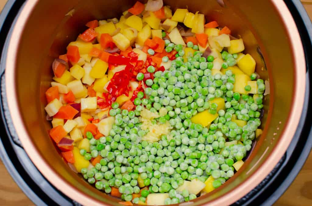 Frozen peas, chopped red chillies and Garlic added to chopped carrots, parsnip, swede and red onion in a pressure cooker pot