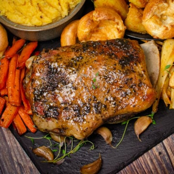 Lamb shoulder coated in mint jelly served with roast potatoes, yorkshire puddings, creamy buttered swede, glazed parsnips, carrots and green peas on a sheet of black slate
