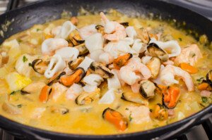 Mussels, prawns and squid rings added to the chowder mixture cooking in a cast iron pan