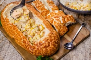 Pouring our creamy fish chowder into a bread bowl with a black ladle served on a wooden chopping board, chunks of bread and two silver spoons on the side.