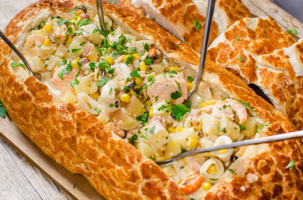Chunks of salmon ,smoked haddock, cod, prawns, squid rings, mussels ,chopped potatoes in a creamy white wine sauce and sprinkled fresh parsley served in a bread bowl with four silver spoons in the middle