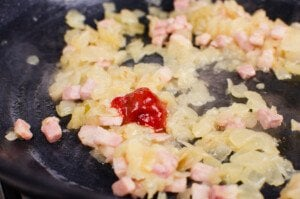 Garlic puree and chilli puree added to the chopped onions and bacon lardons cooking in a cast iron pan