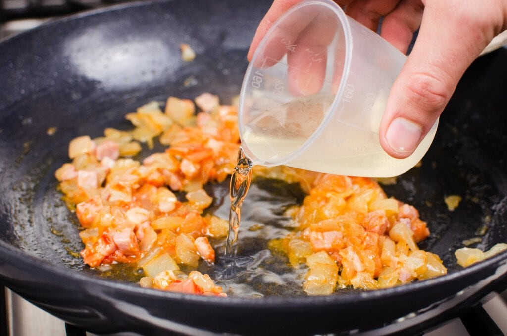 White wine being poured into a cast iron dish whilst cooking chopped onions and bacon lardons