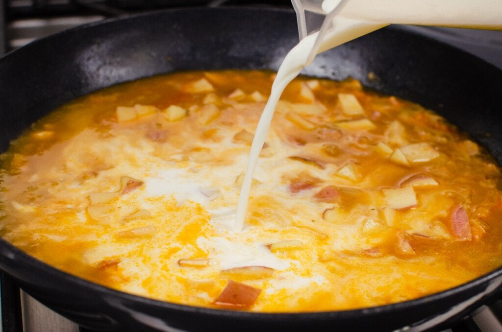 Pouring milk into a cast iron pan and chopped red skinned potatoes placed in the pan to make our chowder