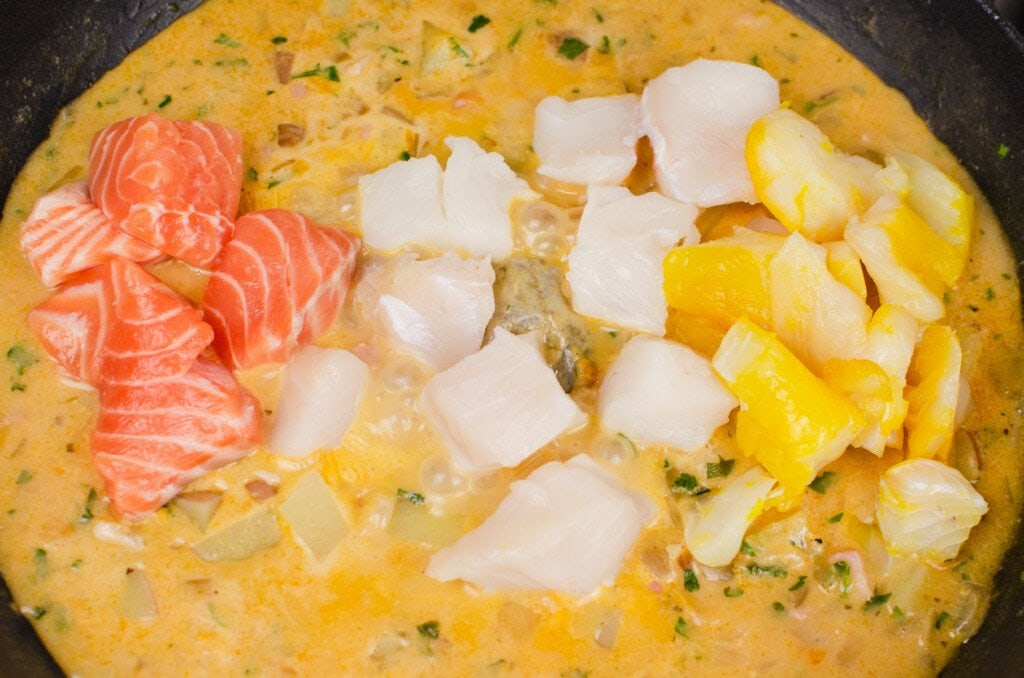 Fish pie mix of chunks of salmon,smoked haddock and cod added to the cast iron pan to make our fish chowder