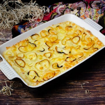Cheese and Mashed Potato Pie with fried onion rings on top served in a black and white casserole dish with a red,white,blue and black cloth and wood shavings in the background