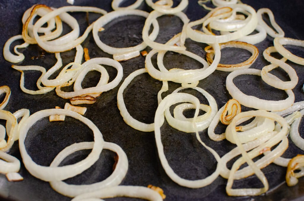 Frying sliced onion rings on a cast iron pan