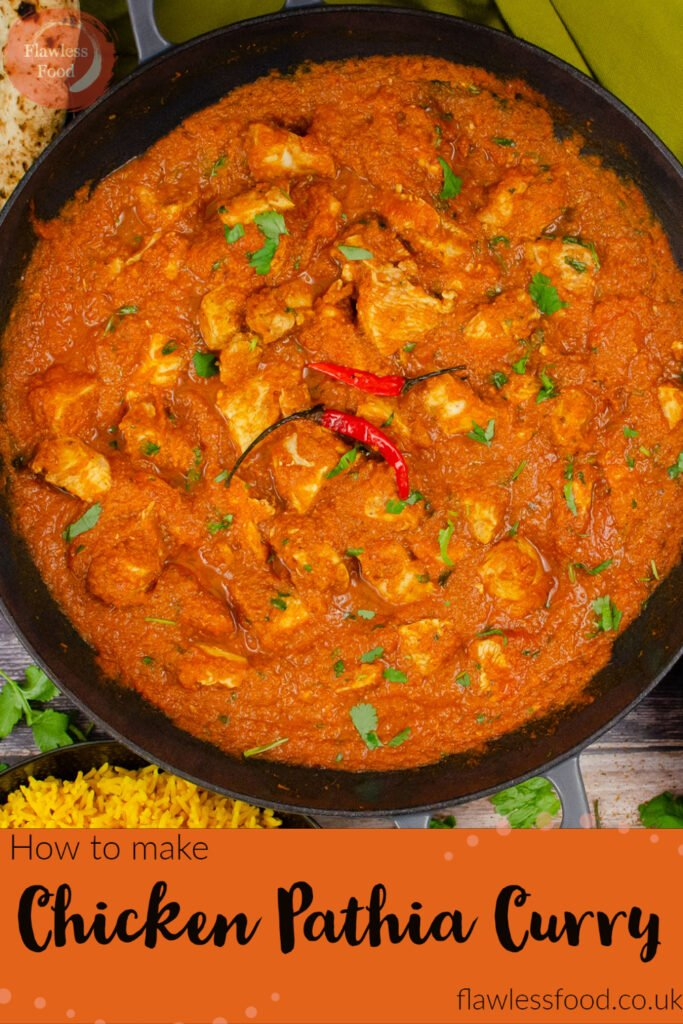Pin image of our Chicken Pathia Curry in a cast iron pan with two red chillies on top and in the background there is a naan bread and pilau rice, served on the side