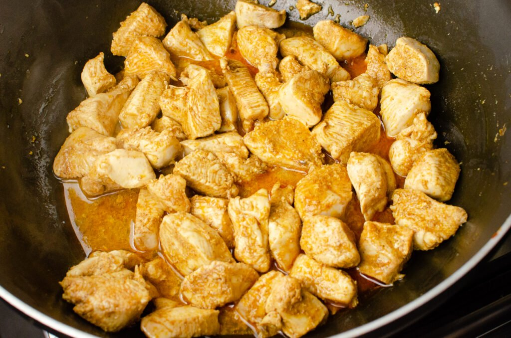 Chopped chicken breast cooking in a pan