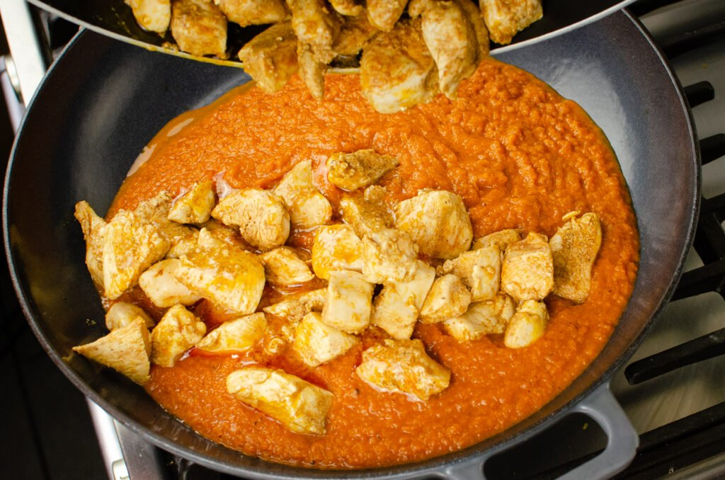Pouring the cooked chicken breast into the pathia curry sauce in a grey iron pan