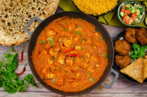 Chicken Pathia Curry in a cast iron pan with two red chillies on top and in the background there is a naan bread, pilau rice, salad onion bhajis and samosa served on the side