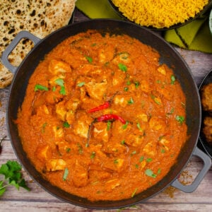 Chicken Pathia Curry in a cast iron pan with two red chillies on top and in the background there is a naan bread, pilau rice, onion bhajis and served on the side