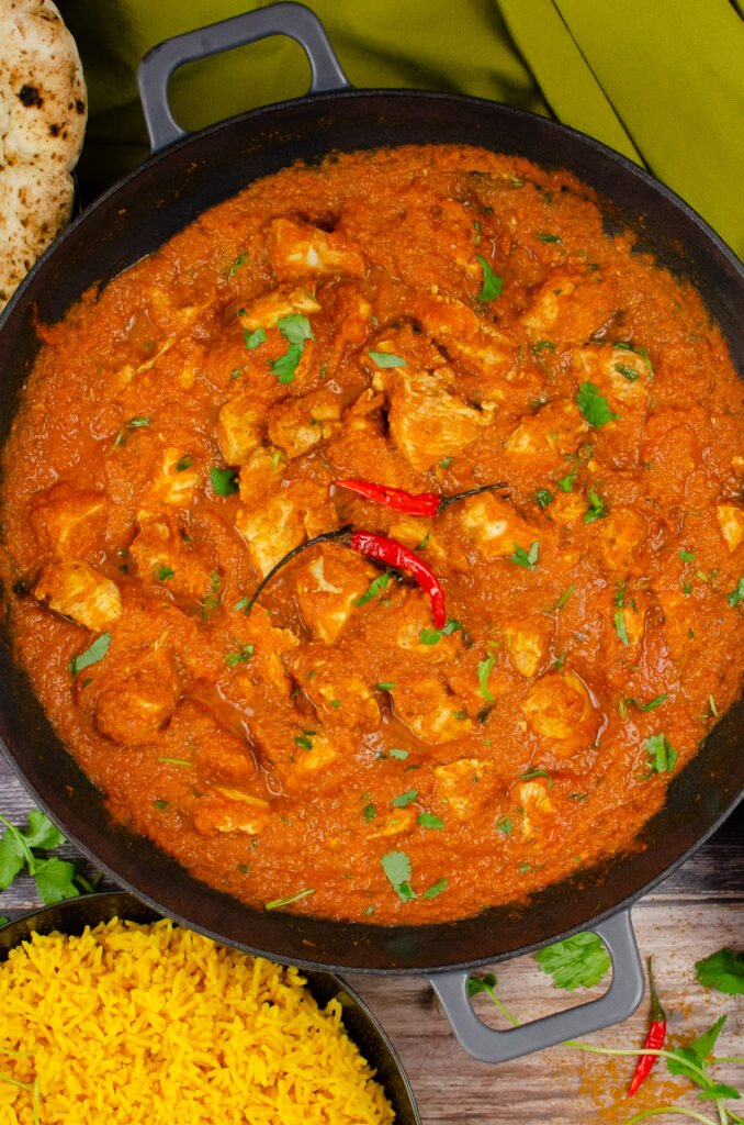 Chicken Pathia Curry in a cast iron pan with two red chillies on top and in the background there is a naan bread and pilau rice, served on the side