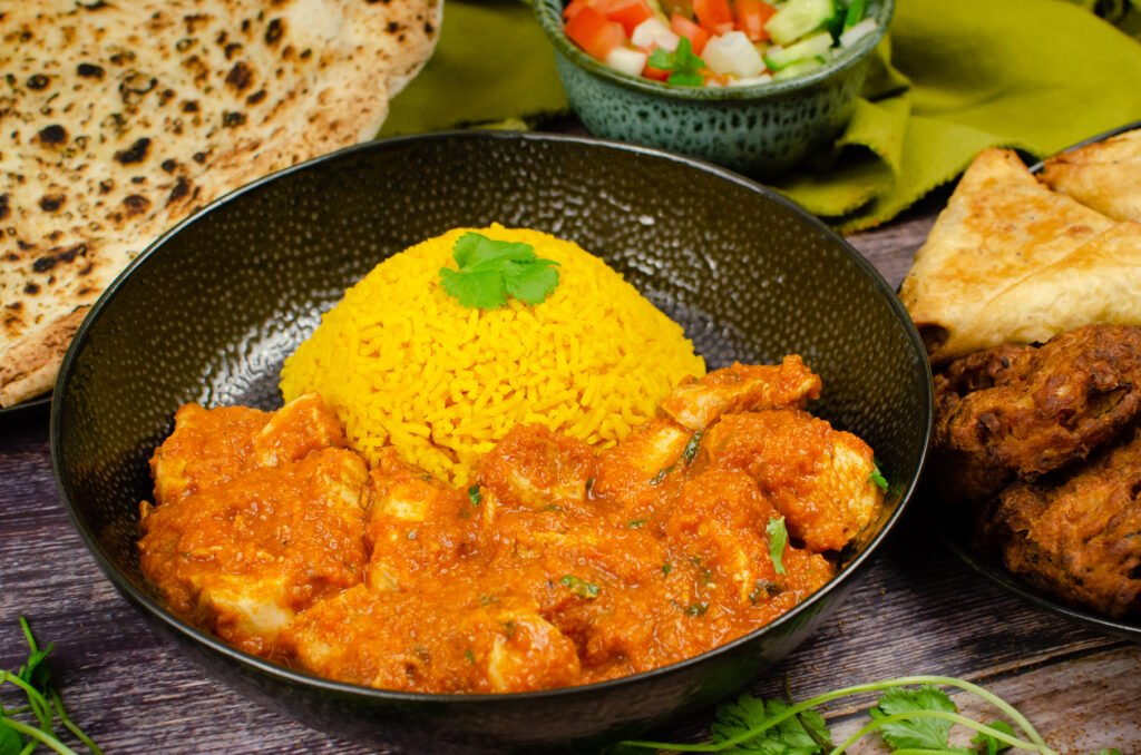 Chicken Pathia Curry in a black bowl served with pilau rice, with naan bread, salad onion bhajis and samosa served on the side