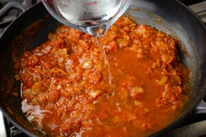 Pouring water into the curry sauce from a clear glass jug into a grey cast iron pan