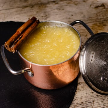 Homemade Apple Sauce served in a copper pot with silver handles and silver lid with a cinnamon stick on top of the pot