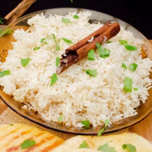 Basmati onion rice served in a glass dish with fresh chopped coriander and a cinnamon stick on top