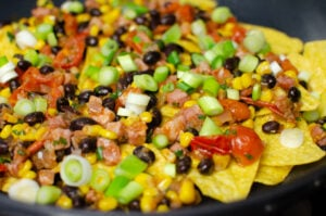 Chopped fresh coriander, Black beans and sweetcorn added to the chopped cherry tomatoes,chopped pancetta ,chopped spring onion and chopped onion on top of nachos in a cast iron pan