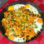 Breakfast Brunch Nachos in a cast iron pan covered in melted cheese and sprinkled with chopped spring onion on red and white towel