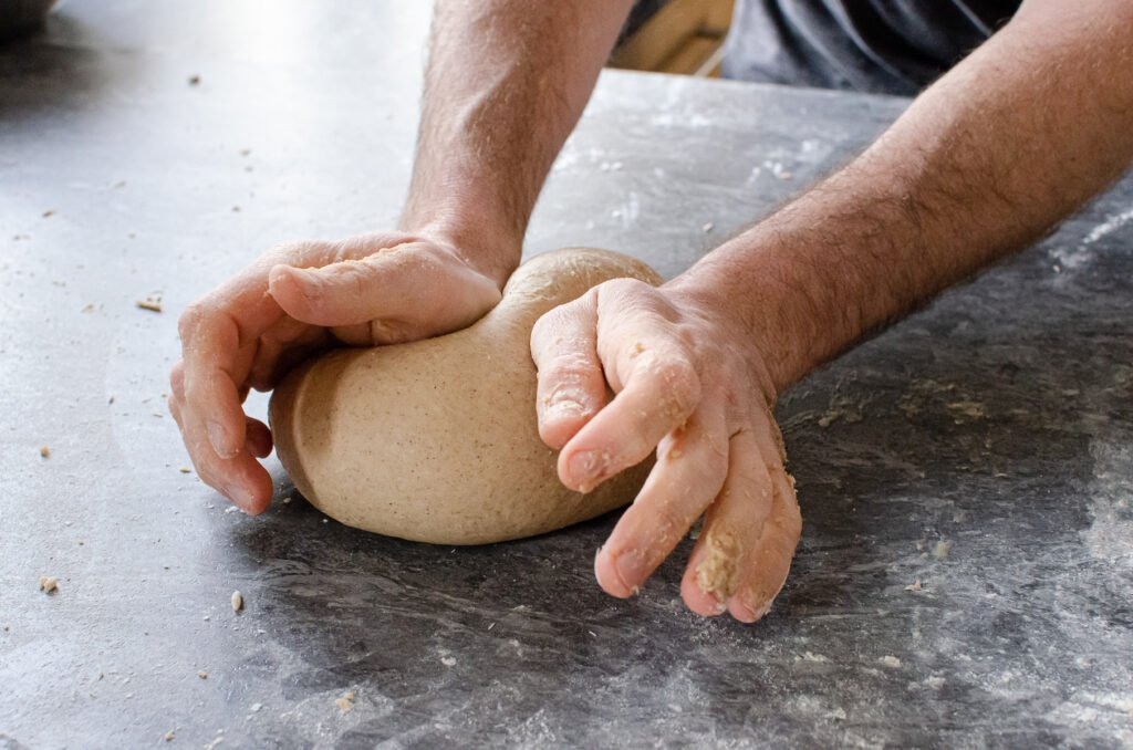 Kneading the dough on a floured surface by hands