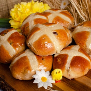 Hot Cross Buns on a wooden board with daffodils and toy chicks around them